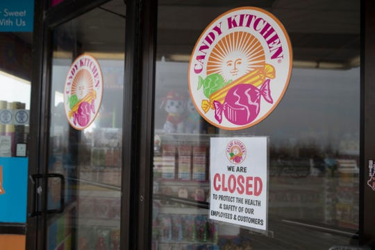 A coronavirus closure sign is taped to the front door of the Candy Kitchen at Rehoboth Beach.
