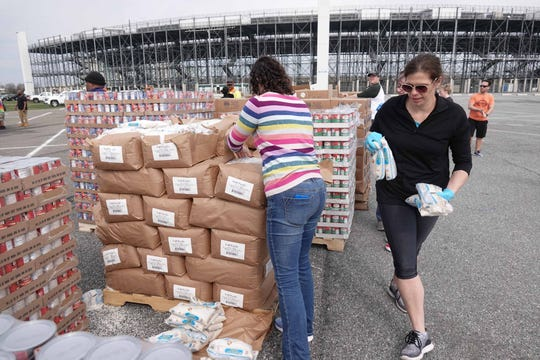 Volunteers and workers for The Food Bank of Delaware prepare food to be given out at the Dover International Speedway's on its third emergency mobile drive-thru pantry on Friday.