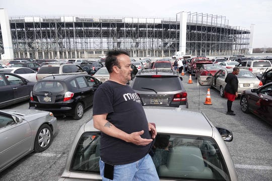 James Flanagan, of Townsend, stands in the back of his pickup truck while waiting with other vehicles at Dover International Speedway's parking lot to receive food from the Food Bank of Delaware on its third emergency mobile drive-thru pantry Friday.