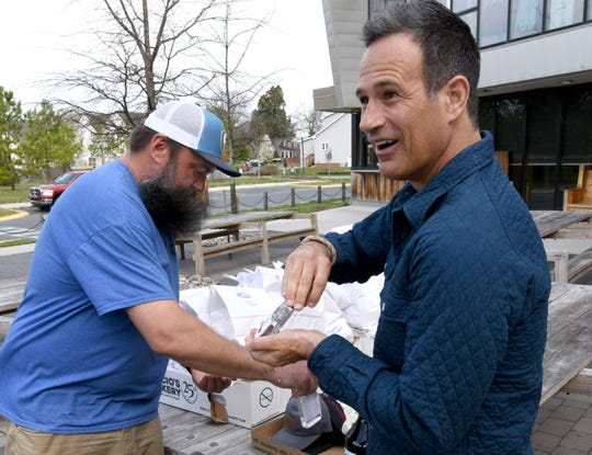 Arena's owner Ramsey Schrader (left) and Dogfish Head Brewery owner Sam Calagione try out freshly brewed hand sanitizer before shanking hands and trading for lunch bags.