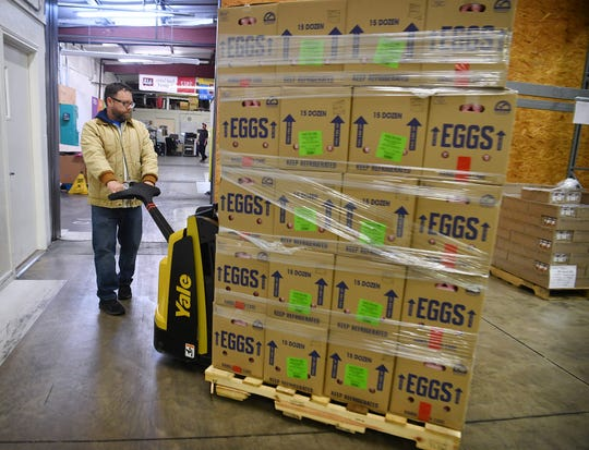 Rusty Williams, operations director for the Wichita Falls Area Food Bank, moves a pallet of fresh eggs in the facility's warehouse Friday.