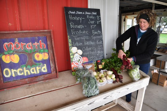 Becky Morath of Morath Orchard sets up a display of items available at their produce stand in Charlie, Texas.
