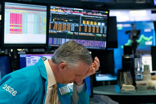 A trader holds his hand to his head after trading was halted at the New York Stock Exchange, Wednesday, March 18, 2020, in New York.