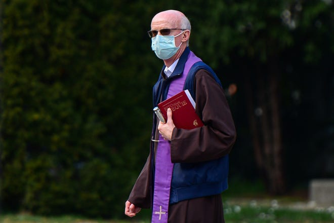 A priest wearing a face mask and holding a funeral rites book of common prayers walks inside the closed Monumental Cemetery of Bergamo, Lombardy, on March 20, 2020 during the country's lockdown aimed at stopping the spread of the COVID-19 (new coronavirus) pandemic.