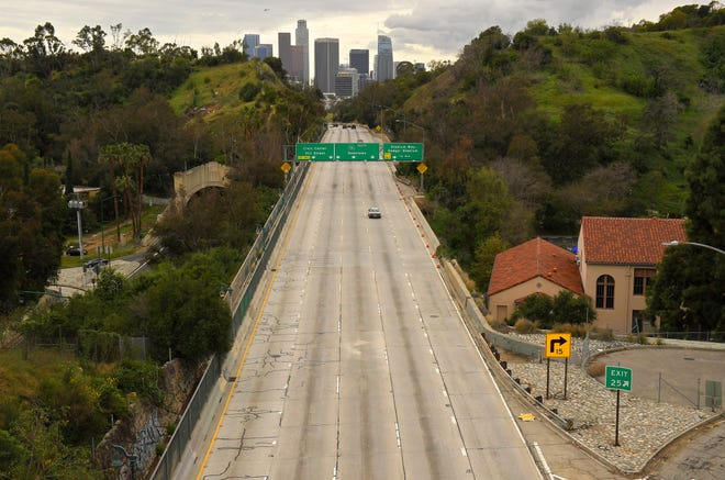 Extremely light traffic moves along the 110 Harbor Freeway toward downtown mid afternoon, Friday, March 20, 2020, in Los Angeles.