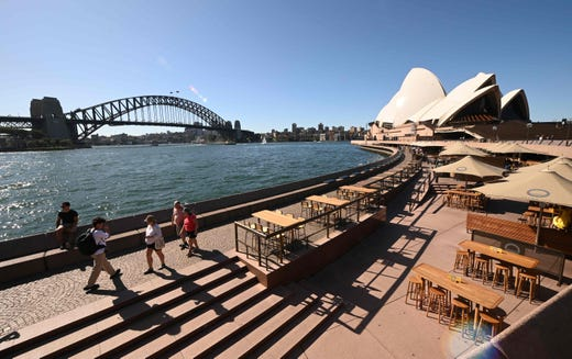 A few tourists walk along Circular Quay in Sydney near the Sydney Opera House on March 20, 2020, after Australia moved to seal off its borders the day before, announcing unprecedented bans on entry for non-residents in the hope of stemming the rise of COVID-19 coronavirus infections.
