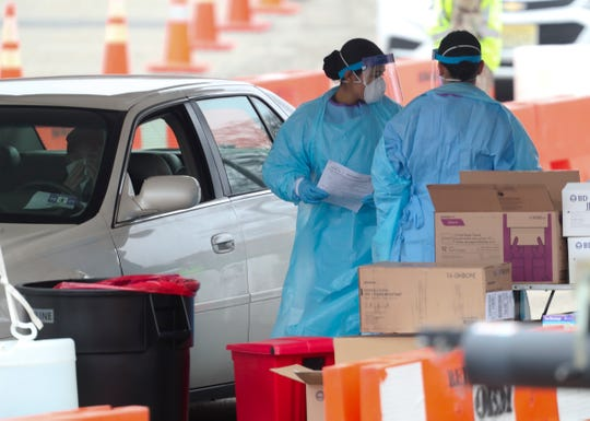 Medical personnel administer tests to New Jersey residents at the drive-through coronavirus testing center at Bergen County Community College in Paramus, New Jersey on Friday, March 20, 2020.