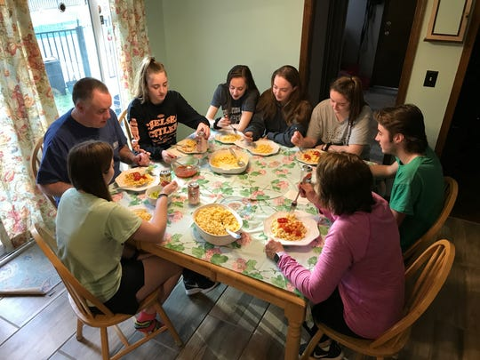 Members of the Keogh family having dinner Friday. The nine of them are making the best of the coronavirus lockdown.
