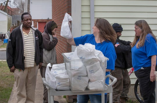Volunteer Roseanne Picciotti and Rev. Rose Broderick hand out packaged lunches to those  that need them outside St. Mark Episcopal Church's soup kitchen in Keansburg. The soup kitchen desperately needs supplies as the number of people they serve has risen dramatically over the past week.