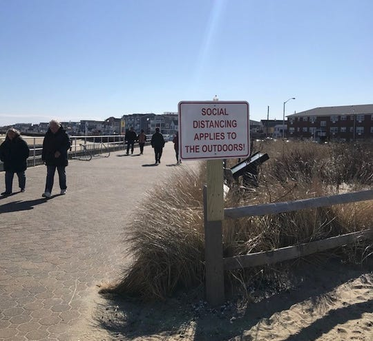 A sign on the boardwalk at the border of Ocean Grove and Bradley Beach warns people to continue practicing social distancing outside.