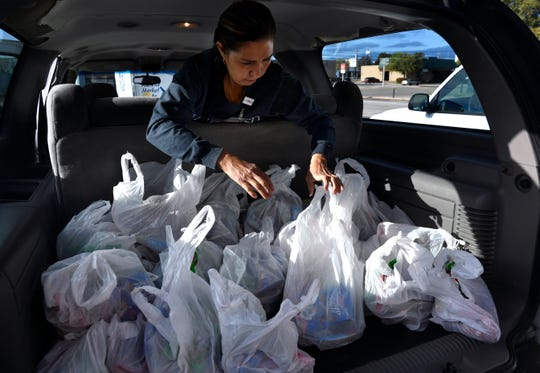 Debbie Romero checks bags of food in the back of an SUV as organizers sort deliveries Friday for Abilene families in need.