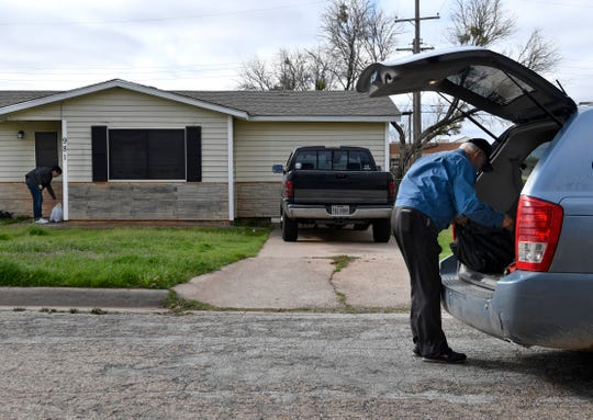 Mel Herweck sorts bags of food as Reporter-News eduction writer Timothy Chipp places a delivery at a front door on an Abilene street Friday.