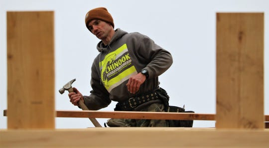 Jeff Orser works on the roof of the new hitting facility being built between the baseball and softball fields at South Kitsap High School. Orser, a starter in the Wolves' 1996 state championship baseball team, has volunteered his time to work on the project.