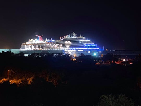"Carnival Breeze cruise ship is lit up with ""We will be back"" message while in Port Canaveral."