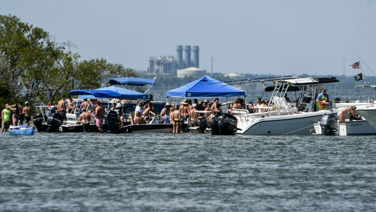 Boaters congregate on a sandbar near a spoil island in the Indian River off SR 528 between Cocoa and Merritt Island Saturday afternoon. The island is a popular gathering place for locals during the summer months.