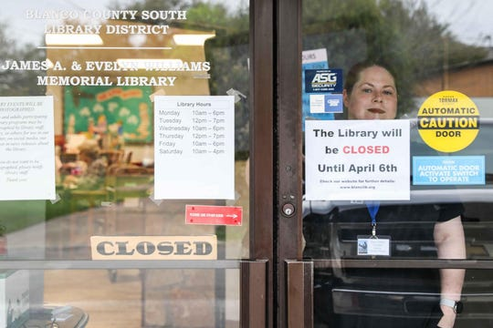Crystal Spybuck, Blanco library director, peers from behind a closed glass door amid the coronavirus outbreak. The library is effectively closed.