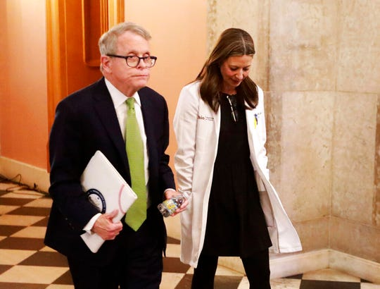 Ohio Gov. Mike DeWine and Ohio Department of Health director Dr. Amy Acton leave the coronavirus news conference in which they announced the first Ohio death on Friday, March 20, 2020 at the Ohio Statehouse. (Doral Chenoweth/The Columbus Dispatch via AP)