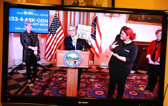 Ohio Gov. Mike DeWine holds up a Columbus Dispatch headline touting neighbors helping neighbors at the beginning of a coronavirus news conference Thursday, March 19, 2020 at the Ohio Statehouse in Columbus, Ohio. Because media are kept in a different room to reduce chances of virus transmission, this picture is taken off a TV. (Doral Chenoweth/The Columbus Dispatch via AP)