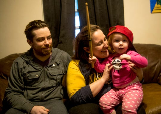 Nicole Gordon, center, picks up she and Bobby Gordon's, left, daughter Cadence Gordon, 1, while Cadence plays with drum sticks at home at the Gordon household in Clarksville, Tenn., on Friday, March 20, 2020. Nicole, who operates a seasonal pool cleaning company, and Bobby, a drummer who performs with bands in Nashville, are out of work due to the COVID-19 coronavirus outbreak.