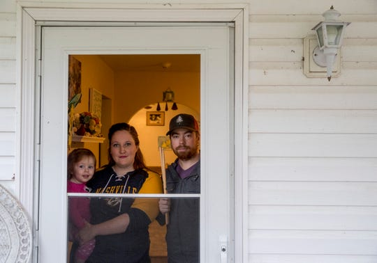 Bobby Gordon, right, Nicole Gordon, center, and their daughter Cadence Gordon, 1, pose for a portrait through their front door at the Gordon Household in Clarksville, Tenn., on Friday, March 20, 2020. Nicole, who operates a seasonal pool cleaning company, and Bobby, a drummer who performs with bands in Nashville, both are out of work due to the COVID-19 coronavirus outbreak.
