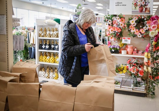 Lori Nielsen of Norwalk takes a bag with a Take and Make mask kit at the JOANN Fabrics and Crafts store in Clive on Saturday.