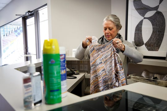 "Silver Fox owner Mary Langen hangs up an outfit at her store on Friday, March 20, 2020, in Des Moines. Langen said she is taking things one day at a time and has been able to stay afloat thanks to loyal customers and putting together ""Fox Boxes"" with personalized outfits in them for people"