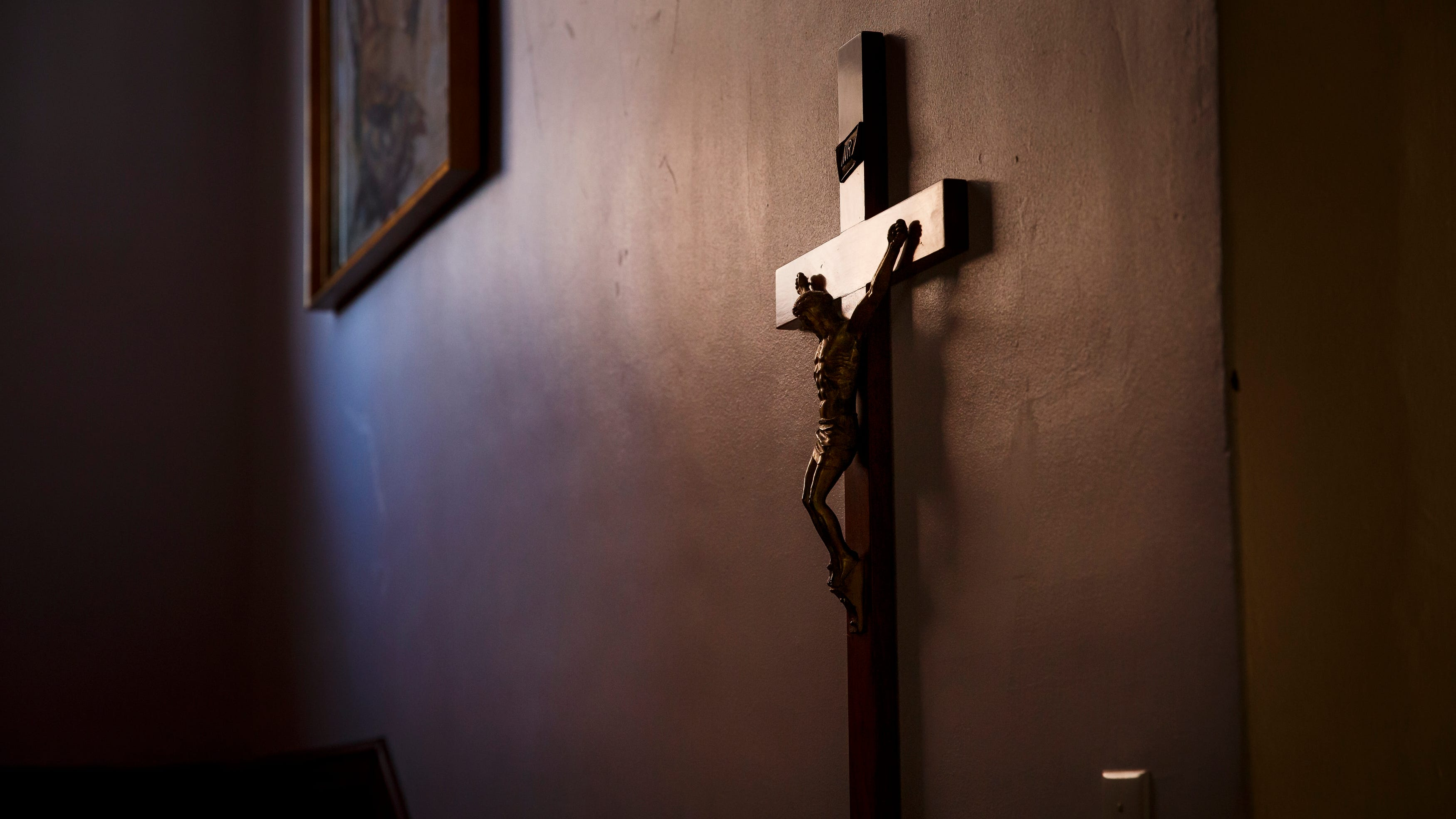 A cross hangs in the hallway as the Rev. Fabian Moncada celebrates Mass in a makeshift chapel as it's streamed live to followers of Our Lady of the Americas Church on Saturday, March 21, 2020, in Des Moines.