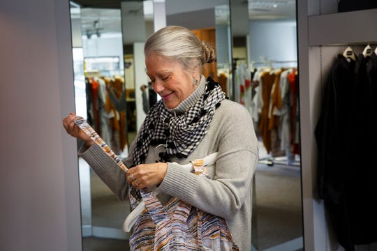 """Silver Fox owner Mary Langen hangs up an outfit at her store on Friday, March 20, 2020, in Des Moines. Langen said she is taking things one day at a time and has been able to stay afloat thanks to loyal customers and putting together """"Fox Boxes"""" with personalized outfits in them for people"""