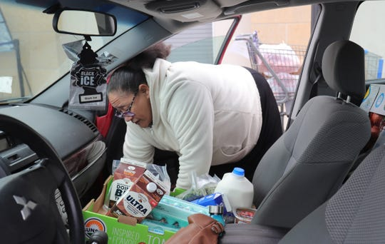 Magna Garcia picks up food from the Gleaners food bank drive-thru in Detroit on Wednesday, March 18, 2020.