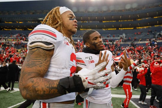 Ohio State defensive end Chase Young, left, and cornerback Jeff Okudah celebrate after defeating Michigan at Michigan Stadium, Nov. 30, 2019.