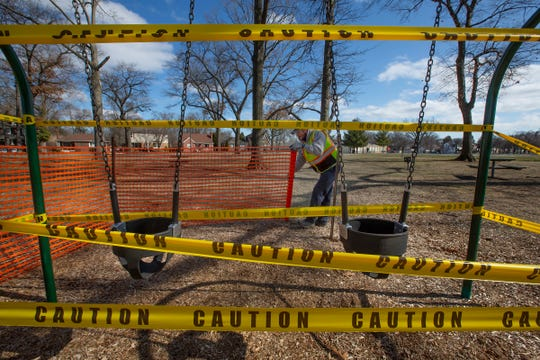 City of Ferndale employee Caleb Clemons, 38, of Ferndale, Michigan erects barriers around a swing set at Garbutt Park on Saturday, March 21 after Oakland County restricted access to playground equipment and closed shopping malls to try and stop the spread of coronavirus.