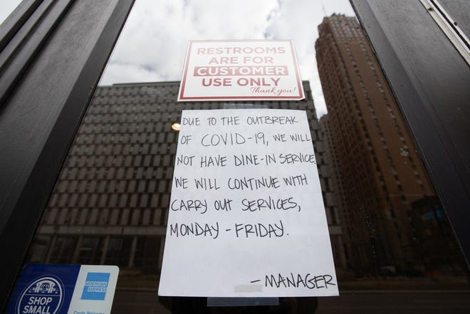 A sign on a downtown Detroit restaurant states the dining room is closed due to COVID-19 on Tuesday, March 17, 2020.