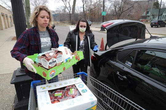 Brook Bianchini helps Jodie Frazier load food she picked up from the Gleaners food bank drive-thru in Detroit on Wednesday, March 18, 2020.