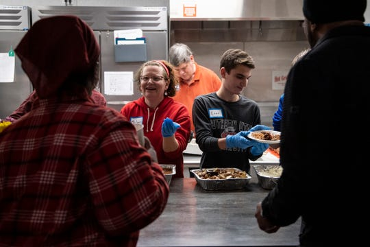 Volunteers Melanie Barash of Sterling Heights and her son Evan, 18, serve dinner to guests at Greenfield Presbyterian Church in Berkley, Wednesday, March 18, 2020.