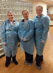 McLaren Northern Michigan nurses, from left,  are Melissa Perry, Karen Gardener and Stacey Forbes, each wearing the Petoskey Plastic isolation gown.