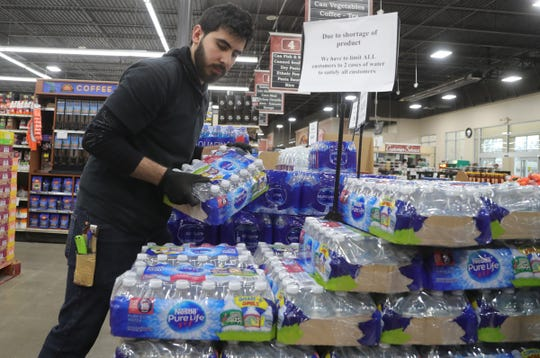 Ferndale Foods employee Fanar Alsaegh stocks water one of the items selling fast due to panic buying caused by the Coronavirus Pandemic Saturday, March 14, 2020.
