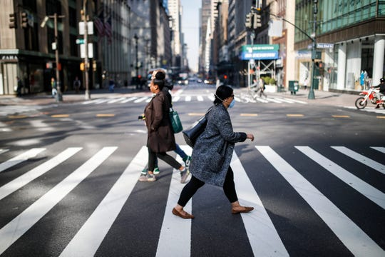 A pedestrian wearing a protective mask hurries across 5th Avenue that is sparsely populated due to COVID-19 concerns, Friday, March 20, 2020, in New York.