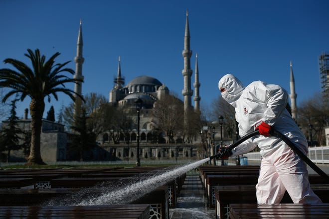 A municipal worker disinfects chairs outside the the historical Sultan Ahmed Mosque, also known as Blue Mosque, amid the coronavirus outbreak, in Istanbul, Saturday, March 21, 2020.