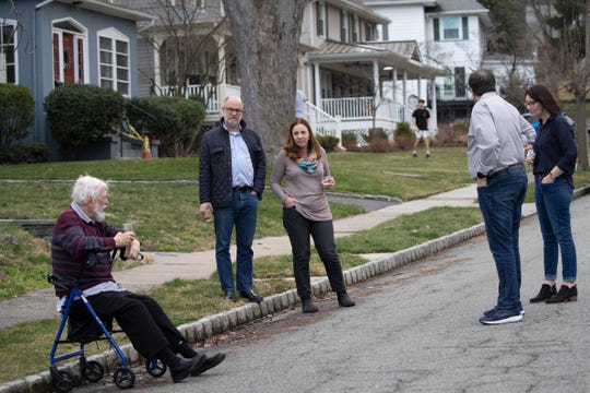 Residents of Brookfield Road in Montclair, N.J., get together for a street happy hour toast Friday, March 20, 2020. With bars shuttered and stressed-out workers stuck at home, companies and friend groups across the U.S. are holding happy hours over video chat to commiserate and keep spirits high amid the new coronavirus pandemic.
