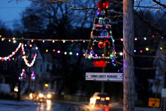 A lit Christmas tree hangs from a pole at dusk as holiday lights illuminate downtown in Farmington, N.H. , on Thursday.