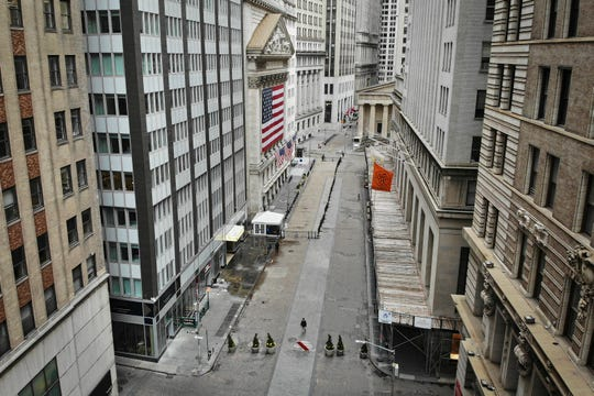A lone pedestrian wearing a protective mask walks past the New York Stock Exchange as COVID-19 concerns empty a typically bustling downtown area, Saturday, March 21, 2020, in New York. New York Gov. Andrew Cuomo announced sweeping orders Friday that will severely restrict gatherings of any size for the state's more than 19 million residents and will require workers in nonessential businesses to stay home. (AP Photo/John Minchillo)