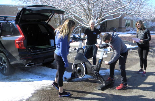Personal trainer Tim Anderson lowers the seat on a stationary bicycle before loading it into the vehicle of Genesis Health Club member Jennifer Datillo, left, Saturday, March 21, 2020, at Genesis' Miramont South location in Fort Collins, Colo.