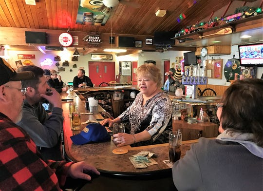 Debbie Crivello grabs a glass to pour a customer a beer at Crivello's on Main in Oconto on March 16, one day before the state ordered restuarants and taverns to close except for take-out and delivery of food. Business after that was very slow, Crivello said.