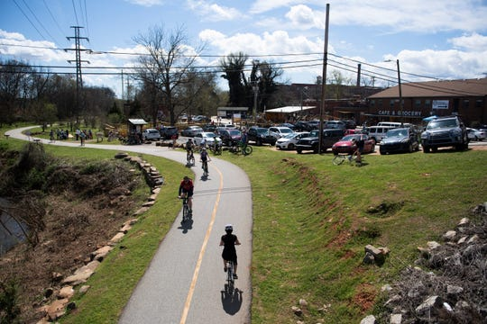 People walk and ride bikes along the Swamp Rabbit Trail Saturday, Mar. 21, 2020.