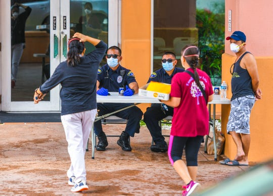 Visitors are greeted by Guam Police Department officers at the entrance to the Hotel Santa Fe in Tamuning on Satruday, March 21, 2020.
