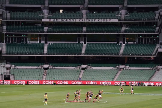 Players from Richmond and Carlton play their Australian Rules Football league game at a empty Melbourne Cricket Ground in Melbourne, Thursday, March 19, 2020, after bans on crowds of more than 500 assembling at outdoor venues amid the coronavirus pandemic. At the MCG less than two weeks ago, more than 86,000 people gathered to watch Australia beat India in the women's Twenty20 Cricket World Cup final. Sports are, evidently, a major part of life in Melbourne, where Aussie rules was invented. (Michael Dodge/AAP Image via AP)