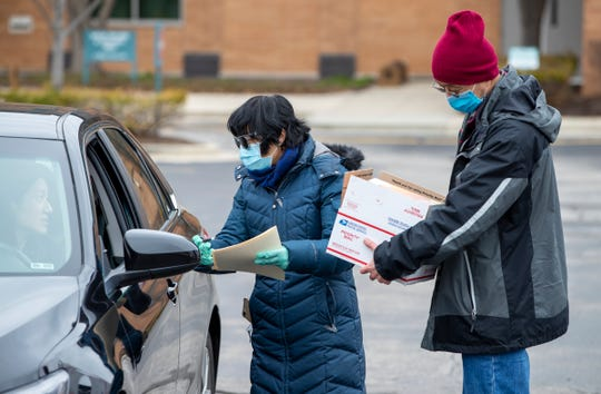 Ya-Hua Hui (left), and Quanbo Xiong, greet a community member who is making a donation during an outreach effort in Carmel by people in the Chinese community, Saturday, March 21, 2020.