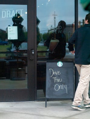 A Starbucks patron at the Baptist Drive location, in Madison, quickly realizes the cafe is closed Saturday, March 21, 2020. On Friday, the Starbucks corporation announced the company will go to drive-through and delivery only for the next two weeks. The company confirmed it will pay U.S. partners for the next 30 days, even if they choose to stay home.