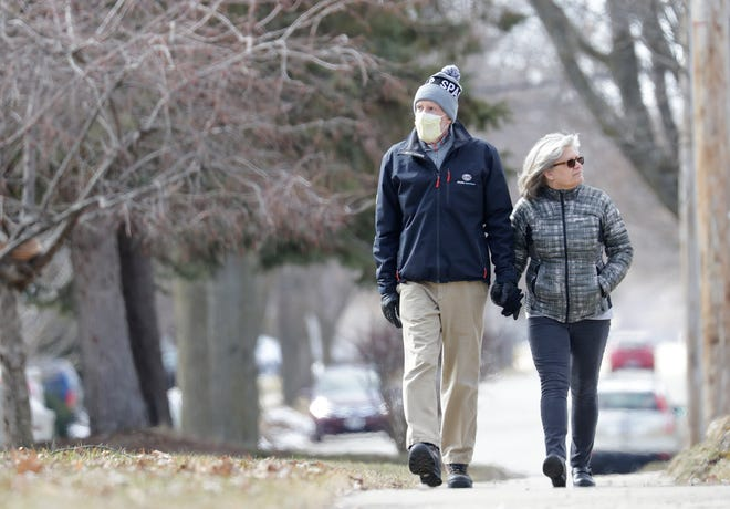 Richard Schoenbohm wears a protective mask as he enjoys a walk with his wife, Sue Bennett, Saturday, March 21, 2020, in Appleton, Wis. Many people are taking extra precautions due to the coronavirus.