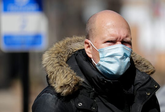 Tom Knight of Oshkosh wears a safety mask due to the coronavirus as he waits for a bus to go shopping Saturday, March 21, 2020, in downtown Oshkosh, Wis.